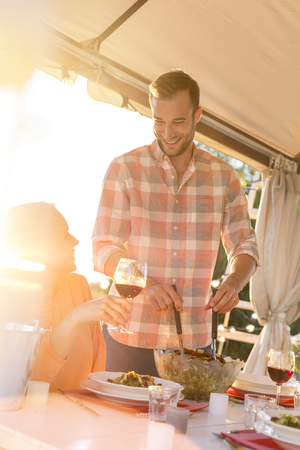 Young man serving salad to wife drinking wine at sunny patio table