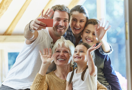 niños platicando: Multi-generation family waving and taking selfie LANG_EVOIMAGES