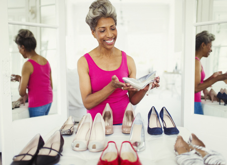 closet: Smiling mature woman looking at high heels in closet