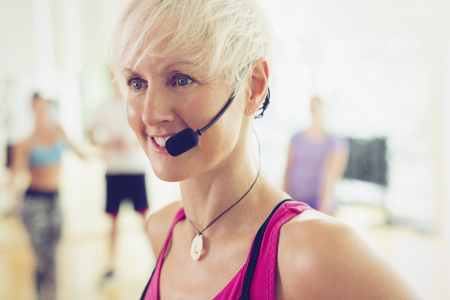 Close up smiling fitness instructor with headset LANG_EVOIMAGES