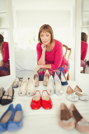indecisive: Indecisive mature woman deciding which shoes to wear in closet