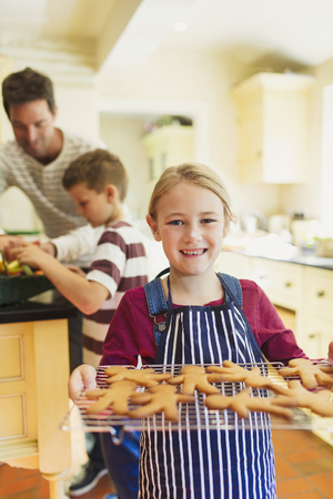 gingerbread man: Portrait smiling girl holding rack of gingerbread cookies