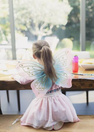 Girl in fairy wings coloring at dining table