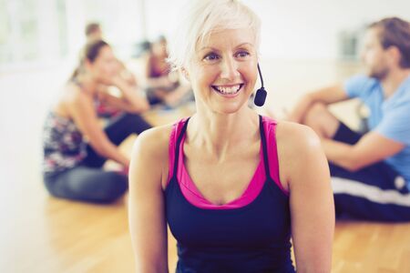 Smiling fitness instructor wearing headset