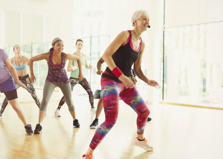 spandex: Energetic fitness instructor leading aerobics class LANG_EVOIMAGES
