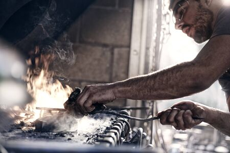 forge: Blacksmith working over fire in forge LANG_EVOIMAGES