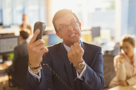 exasperation: Furious businessman gesturing with fist at telephone in office LANG_EVOIMAGES