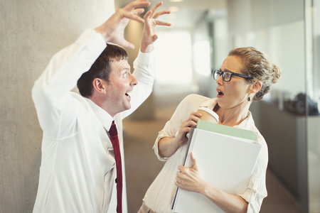 Businessman making snarling gesture at terrified businesswoman LANG_EVOIMAGES