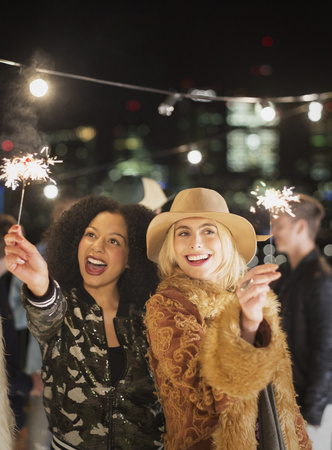 jamaican adult: Young women waving sparklers at rooftop party LANG_EVOIMAGES