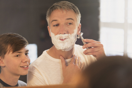 smile close up: Son watching father shave face in bathroom mirror LANG_EVOIMAGES
