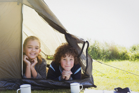 looking away from camera: Portrait smiling brother and sister in tent LANG_EVOIMAGES