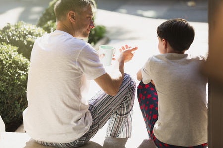 Father with coffee talking to son on front stoop