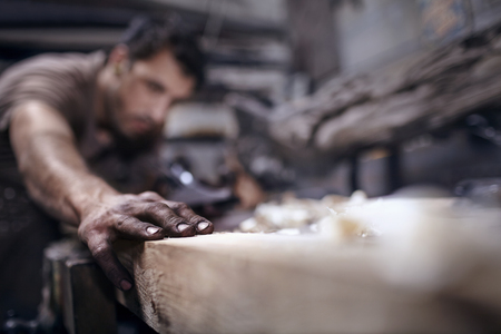 forge: Craftsman chiseling wood in workshop