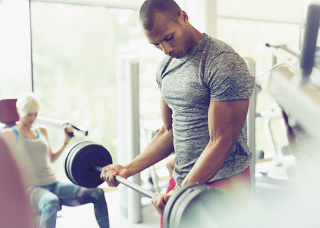 Focused man doing barbell biceps curls at gym LANG_EVOIMAGES