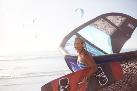 looking away from camera: Portrait woman carrying kiteboard equipment on beach LANG_EVOIMAGES