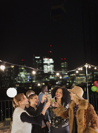 jamaican adult: Young women toasting cocktails at nighttime rooftop party
