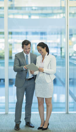 Businessman and businesswoman using digital tablet in office LANG_EVOIMAGES