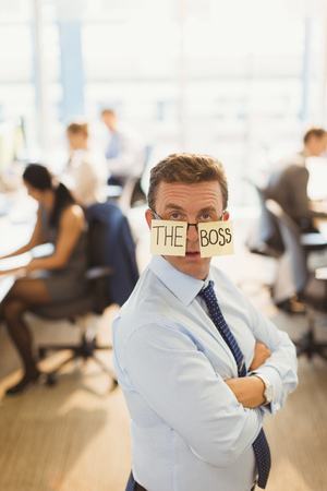 "tough man: Portrait of confident businessman wearing ""The Boss"" eyeglasses in office"