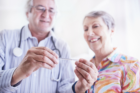 geriatrician: Doctor showing thermometer to senior woman