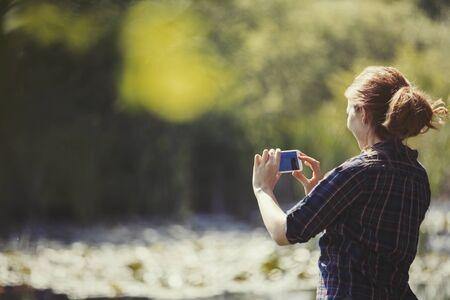 Woman using camera phone at sunny lakeside