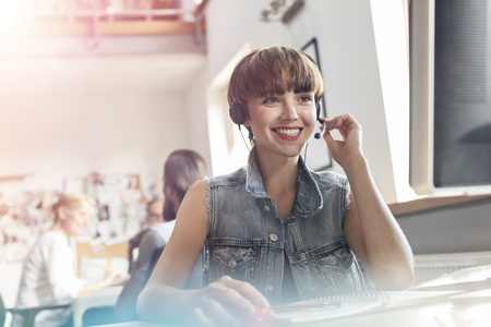 Smiling design professional using headset with microphone in office