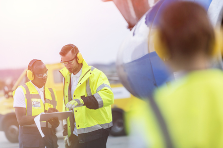 traffic controller: Airport ground crew workers with clipboard talking on tarmac
