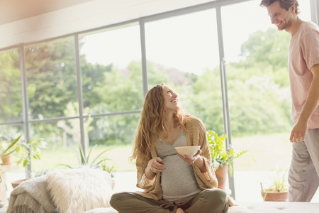 sunroom: Pregnant couple eating in living room LANG_EVOIMAGES