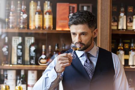 Well-dressed man whiskey tasting