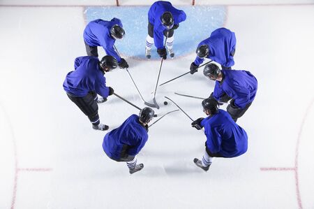 Hockey players in blue uniforms huddling around puck on ice