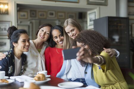jamaican adult: Smiling women friends taking selfie at restaurant table