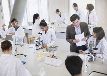 vocational high school: Science professor and college students using microscopes in science laboratory classroom LANG_EVOIMAGES