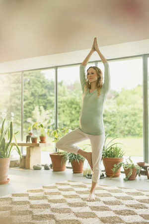 sunroom: Pregnant woman practicing yoga tree pose