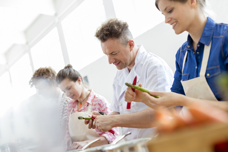 Chef teacher and students peeling asparagus in cooking class kitchen LANG_EVOIMAGES