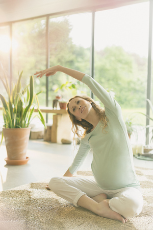 sunroom: Pregnant woman practicing yoga doing side stretch LANG_EVOIMAGES