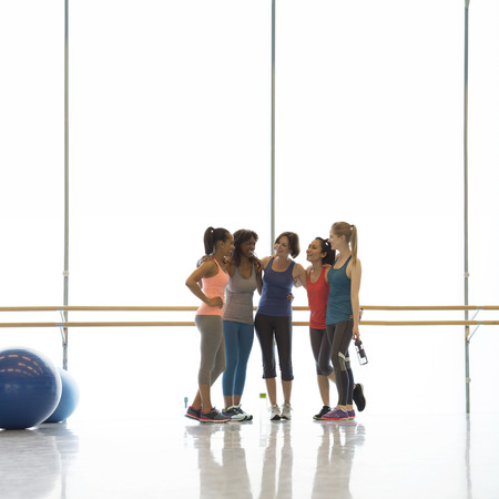 jamaican adult: Smiling women friends talking in exercise class gym studio LANG_EVOIMAGES