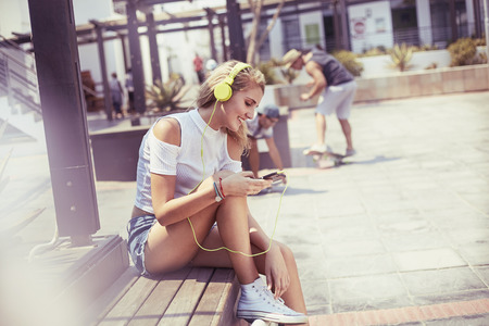 lady on phone: Young woman listening to music with headphones and mp3 player