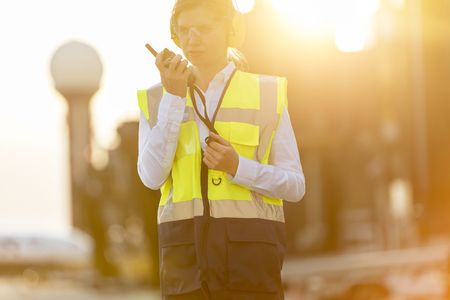 traffic controller: Air traffic controller using walkie-talkie on airport tarmac