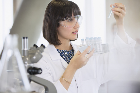 Female college student conducting scientific experiment examining vials in science laboratory classroom LANG_EVOIMAGES
