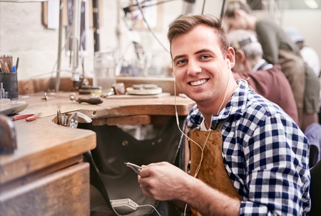 Portrait smiling male jeweler working listening to music with headphones in workshop