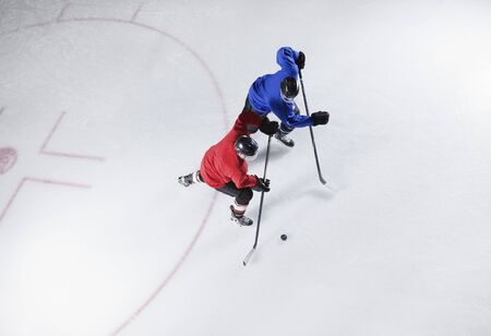 padding: Hockey players going for the puck on ice LANG_EVOIMAGES