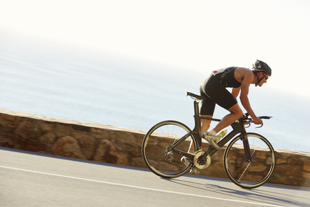 road position: Male triathlete cyclist racing on ocean road