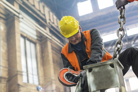 Steel worker fastening crane chain to steel in factory LANG_EVOIMAGES