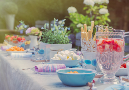 Strawberry water and desserts on garden party patio table LANG_EVOIMAGES