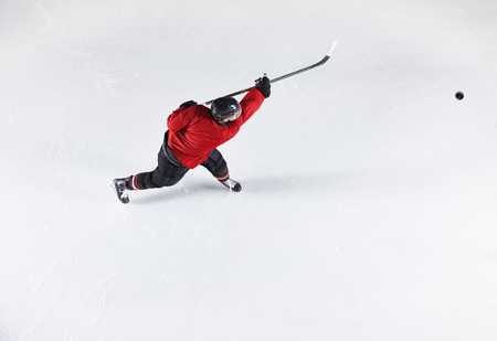 Hockey player in red uniform shooting puck on ice LANG_EVOIMAGES