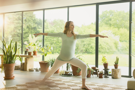 sunroom: Pregnant woman practicing yoga warrior 2 pose