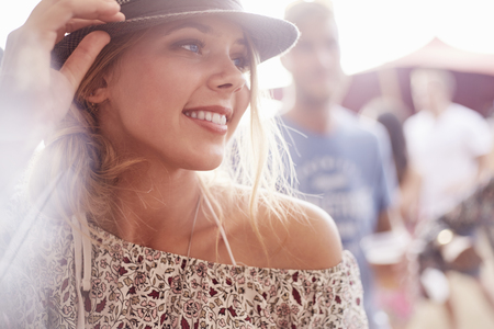 Close up smiling young blonde woman at music festival