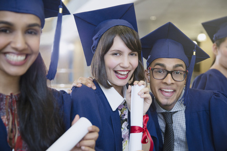 Portrait enthusiastic college graduates in cap and gown posing with diploma LANG_EVOIMAGES