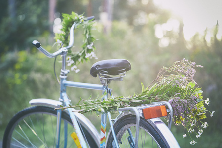 transportation: Flowers and garland on bicycle in garden