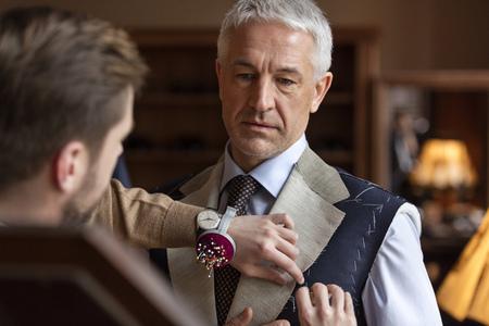 Tailor fitting businessman for suit in menswear shop LANG_EVOIMAGES