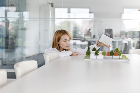 Female architect arranging model in conference room